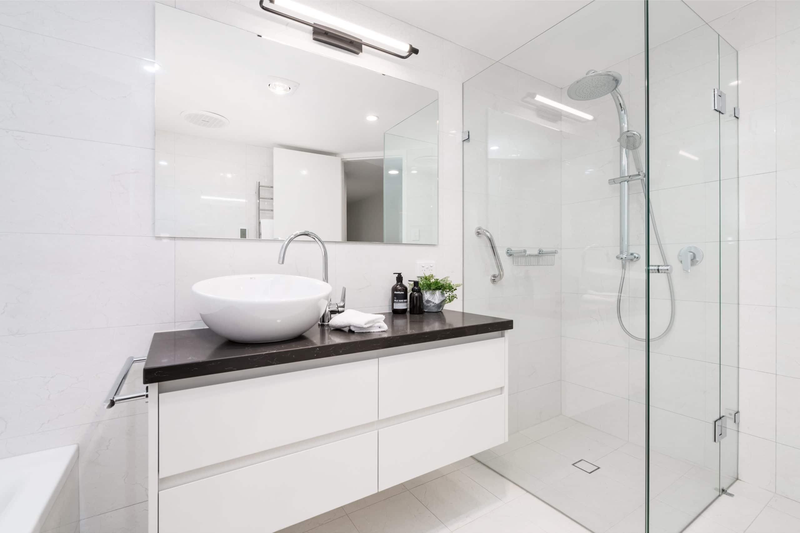 Moderne Badsanierung. Weißes Badezimmer mit der Dusche. Glassdusche
